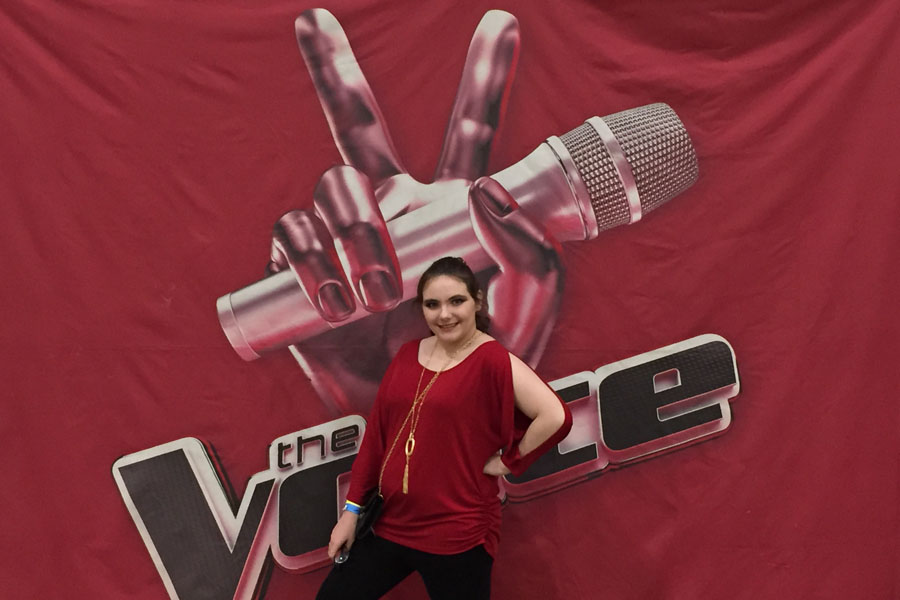 Elizabeth Hall poses in front of The Voice logo before her audition.