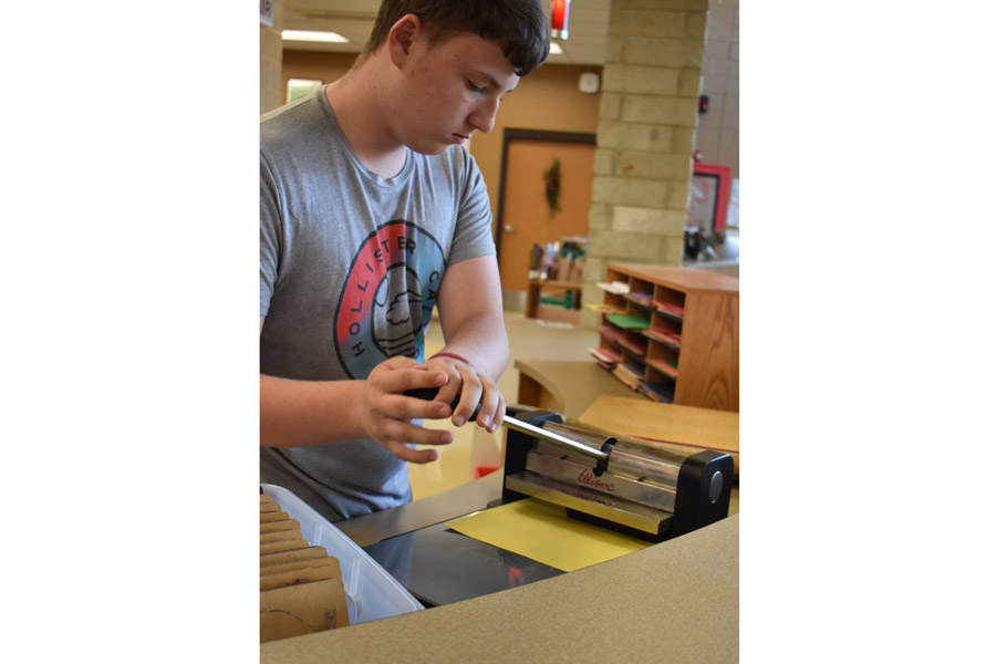 Jared Howard, 11th, uses the letter cutter in the Makerspace for a class project.