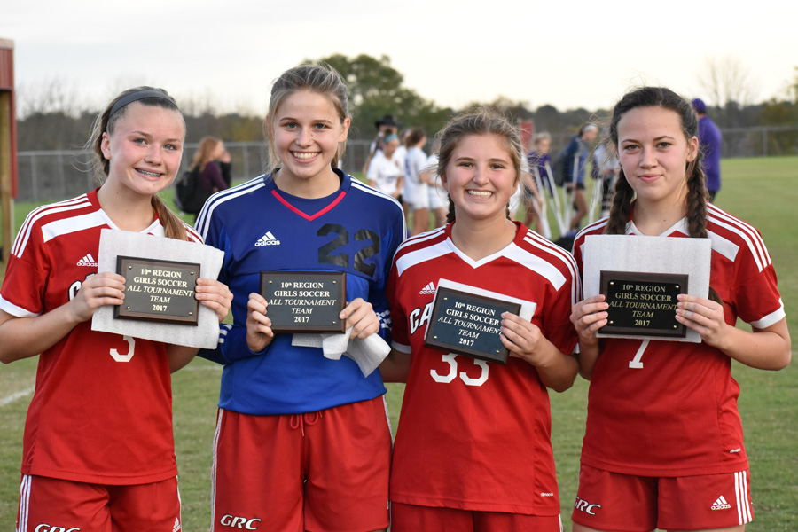 From left, Delaney Manning, Laura Martin, Maddie Mann, and Allie Bush hold their All Tournament Team plaques.