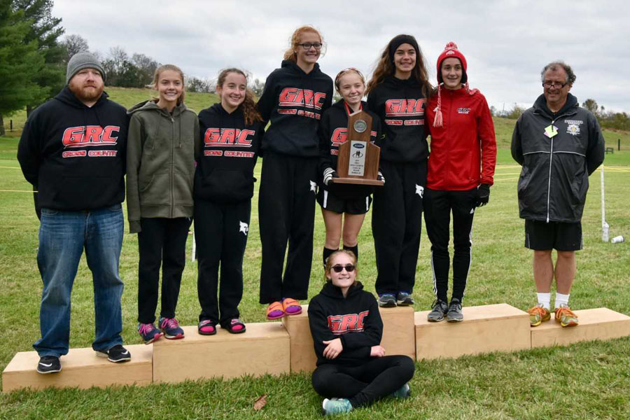 Girls' Cross Country team poses with Region trophy.