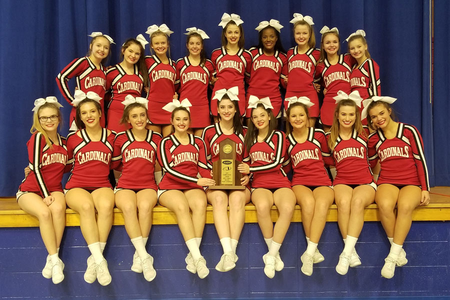 Cheerleaders pose with the Region Championship trophy.
