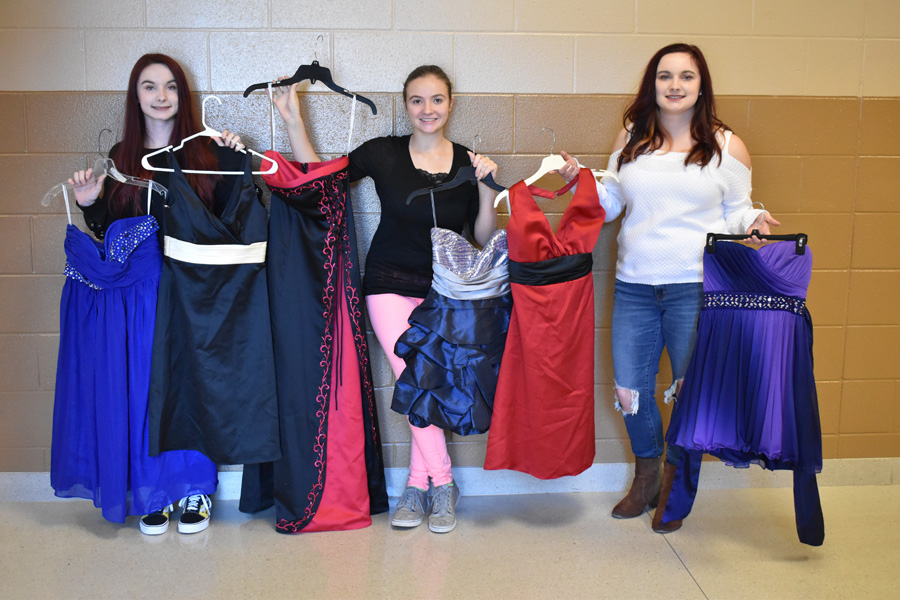 From left, Shana Rose, Haily Bush, and Katie Rose pose with the dresses.