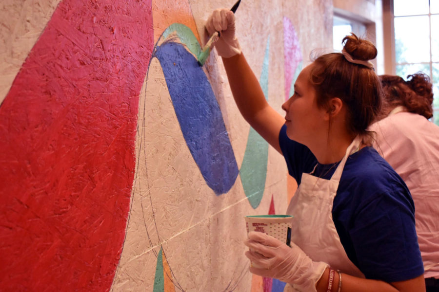 Mckenzie Crowl works on the mural in the 100s hallway.